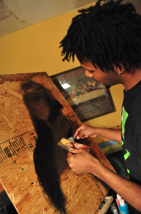 Artist painting a picture on wood.